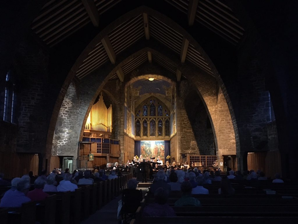 Choir in St Andrew's Church. A large choir dressed in black are stood towards the altar of the church. The altar is lit and the nave is in darkness.